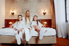 Den lyckliga modern och barn av kopplar samman sammanträde på sängen, fot arkivbild