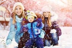 Den lyckliga modern och barn i vinter parkerar Royaltyfri Foto
