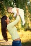 Den lyckliga modern och behandla som ett barn att spela utomhus Royaltyfri Foto