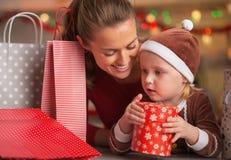 Den lyckliga modern och behandla som ett barn bland julshoppingpåsar Arkivbilder