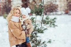 Den lyckliga modern och behandla som ett barn dottern som går i snöig vinter, parkerar Fotografering för Bildbyråer