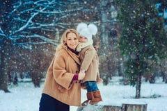 Den lyckliga modern och behandla som ett barn dottern som går i snöig vinter, parkerar Arkivbild