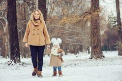 Den lyckliga modern och behandla som ett barn dottern som går i snöig vinter, parkerar Arkivbilder