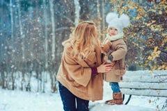 Den lyckliga modern och behandla som ett barn dottern som går i snöig vinter, parkerar Royaltyfri Fotografi
