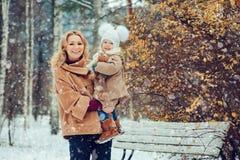 Den lyckliga modern och behandla som ett barn dottern som går i snöig vinter, parkerar Arkivfoton