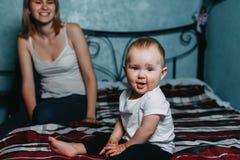 Den lyckliga modern och behandla som ett barn dottern som spelar hemmastadd säng arkivfoto