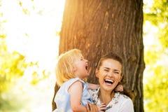 Den lyckliga modern och behandla som ett barn flickan som står det near trädet royaltyfri fotografi