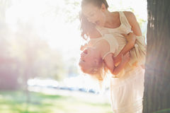 Den lyckliga modern och behandla som ett barn ha det roliga near trädet Royaltyfria Foton
