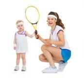 Den lyckliga modern och behandla som ett barn hållande tennisracket Arkivbild