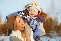 Den lyckliga modern och behandla som ett barn i vinter parkerar Royaltyfri Bild
