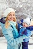Den lyckliga modern och behandla som ett barn i vinter parkerar Fotografering för Bildbyråer