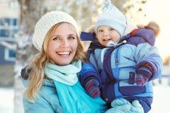 Den lyckliga modern och behandla som ett barn i vinter parkerar Royaltyfria Foton