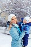 Den lyckliga modern och behandla som ett barn i vinter parkerar familj utomhus arkivfoto