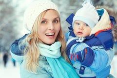 Den lyckliga modern och behandla som ett barn i vinter parkerar familj utomhus arkivfoton