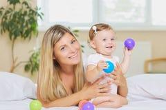 Den lyckliga modern och behandla som ett barn inomhus Royaltyfri Foto