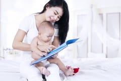 Den lyckliga modern och behandla som ett barn läsa en bok Arkivbild