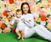 Den lyckliga modern och behandla som ett barn på gräset Arkivfoton
