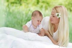 Den lyckliga modern och behandla som ett barn på naturlig bakgrund Arkivfoto