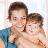 Den lyckliga modern och behandla som ett barn pojken Arkivbild