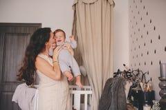 Den lyckliga modern och behandla som ett barn sonen som tillsammans hemma spelar, mammainnehavet och kysser henne 11 månad den ga Arkivfoto