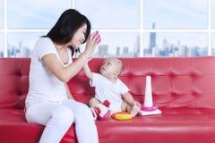 Den lyckliga modern och behandla som ett barn spela leksaker hemma Arkivbild