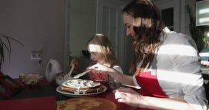 Den lyckliga modern och dottern förbereder en födelsedagkaka stock video