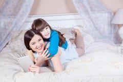 Den lyckliga modern och dottern lägger i säng med den digitala minnestavlan fotografering för bildbyråer