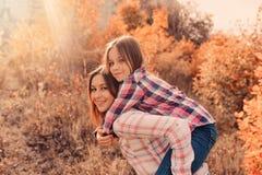 Den lyckliga modern och dottern på slags tvåsittssoffa går på soligt fält Royaltyfria Foton