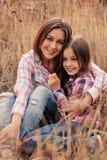 Den lyckliga modern och dottern på slags tvåsittssoffa går på soligt fält Arkivbild