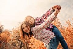 Den lyckliga modern och dottern på slags tvåsittssoffa går på soligt fält Royaltyfri Bild