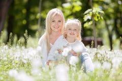 Den lyckliga modern och dottern som kopplar av i, parkerar Sk fotografering för bildbyråer