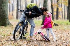 Den lyckliga modern och dottern som rider cyklar i höst, parkerar royaltyfria foton