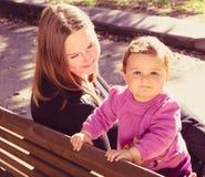 Den lyckliga modern och dottern spelar på en parkera Royaltyfri Bild