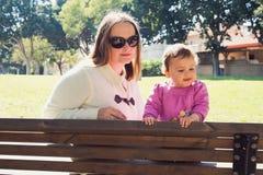 Den lyckliga modern och dottern spelar på en parkera Royaltyfria Bilder