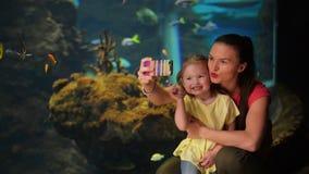 Den lyckliga modern och dottern tar Selfie Akvariet med fiskar är på bakgrund De har mycket gyckel denna moder` s lager videofilmer