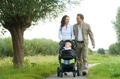 Den lyckliga modern och fadern som går med, behandla som ett barn i pram Arkivbild
