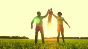 Den lyckliga modern och fadern som rymmer händer för barn` ett s, lyfter det, mot bakgrunden av solnedgången Begreppet av ett lyc arkivfilmer
