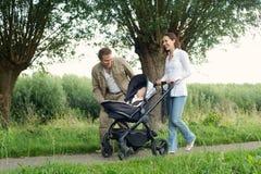 Den lyckliga modern och fadern som utomhus går med, behandla som ett barn i pram Arkivbilder
