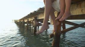 Den lyckliga modern och hennes dottersammanträde på en träpir och dinglar fot över vattnet arkivfilmer