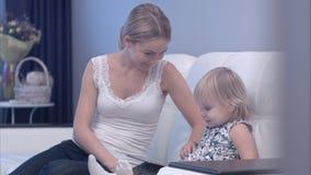 Den lyckliga modern och hon behandla som ett barn barnet som använder minnestavlan royaltyfri bild