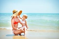 Den lyckliga modern och hon behandla som ett barn dottern på havskust royaltyfri foto
