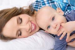 Den lyckliga modern och hon behandla som ett barn sonen som tillsammans ligger på en säng lycklig familj nyfödd barnmoder arkivbilder