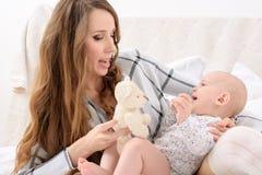 Den lyckliga modern och hon behandla som ett barn sonen som tillsammans spelar på en säng lycklig familj nyfödd barnmoder Royaltyfri Fotografi