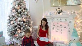 Den lyckliga modern och den lilla sonen ser gåvor i den nya festliga inre för års` s arkivfilmer