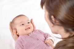 Den lyckliga modern rymmer på händer av det nyfött behandla som ett barn Royaltyfria Foton