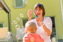 Den lyckliga modern som blåser bubblor för henne, behandla som ett barn Royaltyfria Bilder