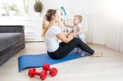 Den lyckliga modern som gör yoga med hennes, behandla som ett barn pojken på golv på den bosatta rooen Arkivbild
