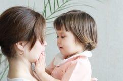 Den lyckliga modern som kramar barnet, den fysiska kontakten, familjförhållanden som kelar behandla som ett barn för fysisk affek Arkivbild