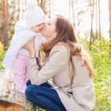 Den lyckliga modern som kysser henne, behandla som ett barn på utomhus-, höst parkerar Fotografering för Bildbyråer