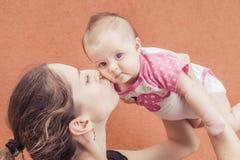 Den lyckliga modern som kysser henne, behandla som ett barn på väggbakgrund Arkivbilder